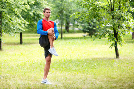 Sport and healthy lifestyle concept - jogger man stretcing muscles.