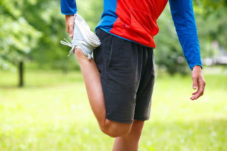 Sport and healthy lifestyle concept - jogger man stretcing muscles. Close up view of a legs.