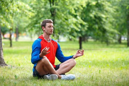 Young man meditating in a public park.