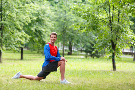 Young man stretches muscles outdoor in public park.