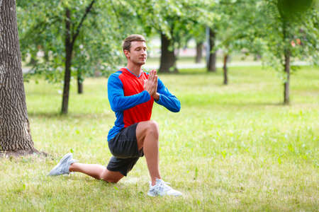 Young man doing yoga exercises in a public park.