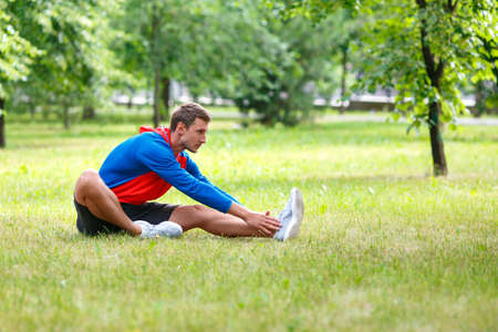 Man stretches outdoor in summer time. Sitting on a green grass.