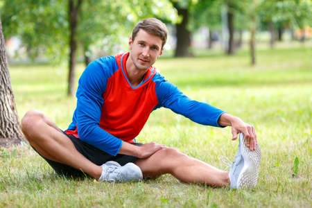 Man stretches muscles outdoor. Waming up in public park.