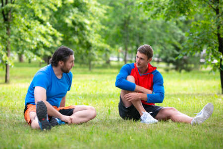 Two friends taking rest after workout in public park. Standard-Bild - 150068967