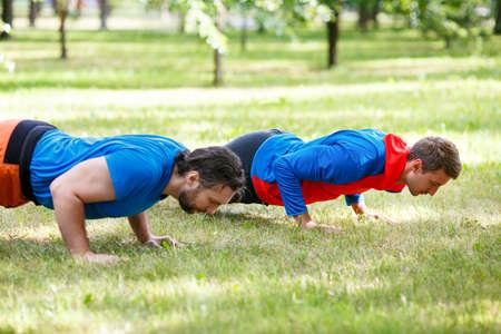 Two men doing push-up in public park. Cropped image. Standard-Bild