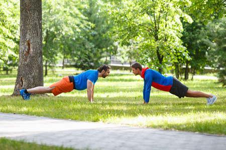 Two men do push-ups opposite each other in a public park. Standard-Bild - 150120618