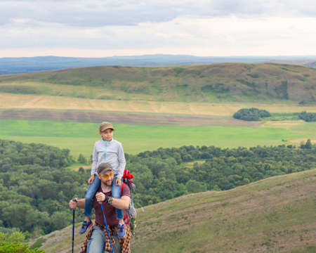 Daughter sits on fathers shoulders in travel.