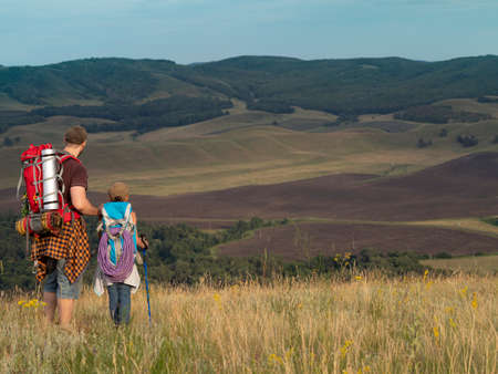 Father and daughter walking by top of hill with backpacks, travel in nature. Standard-Bild