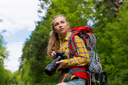 Female hiker looking by side and holding photocam with both hands. Standard-Bild