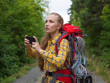 Female hiker looking at her mobile phone holding it with both hands. Standard-Bild - 150944874