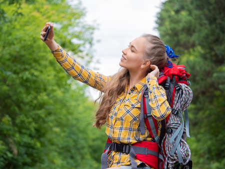 Hiker woman make a selfie with mobile phone.