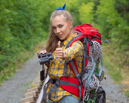 Hiker woman with binokular looking at camera and keeping thumb up.