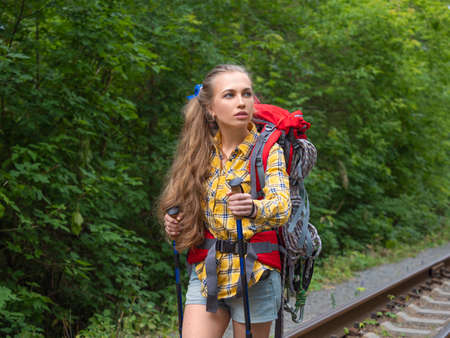 Hiker woman goes by rail through the forest.