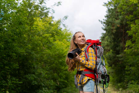 Smiley female hiker woman looking by side and holding photocam. Standard-Bild - 150944892