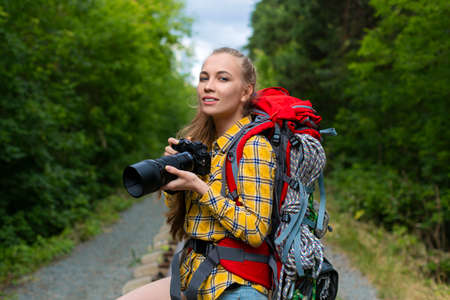 Smiley female hiker woman with photocamera looking at you.