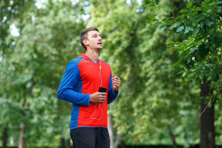 Male jogger is training in the park and listening to the music.