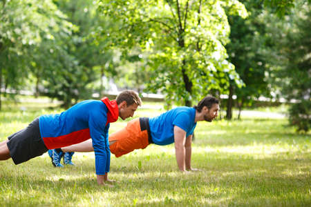 Two men doing pushups outdoor. Selective focus. Standard-Bild - 150777396