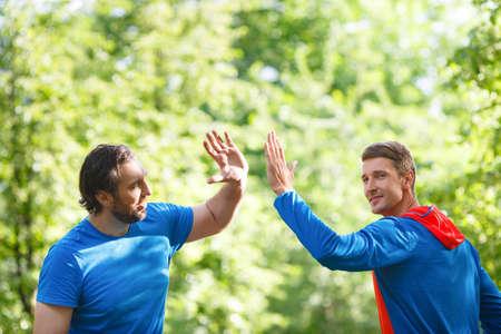 Two men after workout outdoor giving high five. Standard-Bild