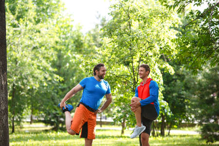 Two men warming up muscles before jogging outdoor.