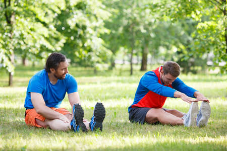 Two men stretching muscles after jogging outdoor. Standard-Bild - 150771249