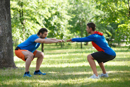 Two men warming up muscles before jogging.