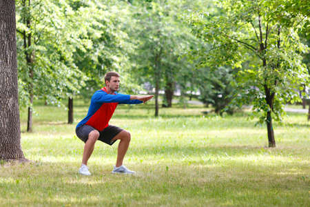 Workout outdoor. Waming up muscles in public park. Standard-Bild