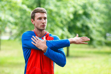 Front view of a sportsman stretching hands while standing outdoor in a park and looking by side. Close up cropped photo. Standard-Bild - 150773146