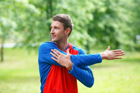 Front view of a sportsman stretching hands while standing outdoor in a park and looking by side. Standard-Bild - 150777400