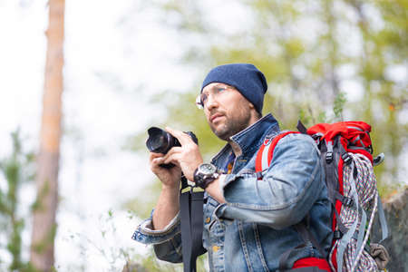 Middle aged bearded male hiker with photocamera.