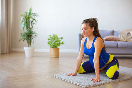 Pregnant woman doing relaxation exercises at home.