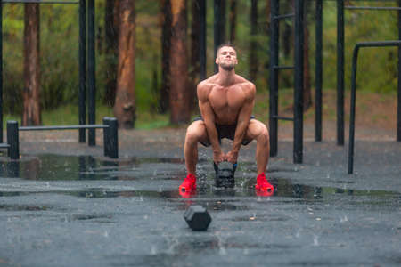 Sportsman during hard workout outdoor in a rainy day.