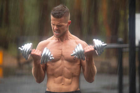 A man is training with dumbbells in the rain. 版權商用圖片