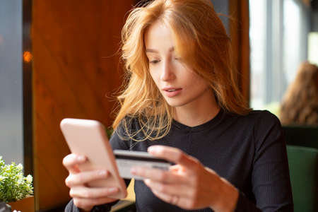 Red haired young woman making card payment through mobile phone to pay bills. Close up.