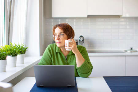 Thoughtful senior woman with a cup of warm tea working from home using laptop. Banco de Imagens