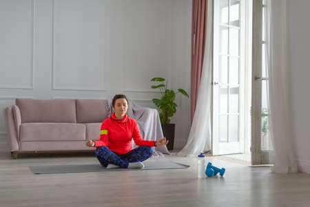 Middle-aged woman meditates at home.