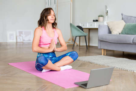Online video lesson with a coach - woman meditates in front of a laptop monitor.