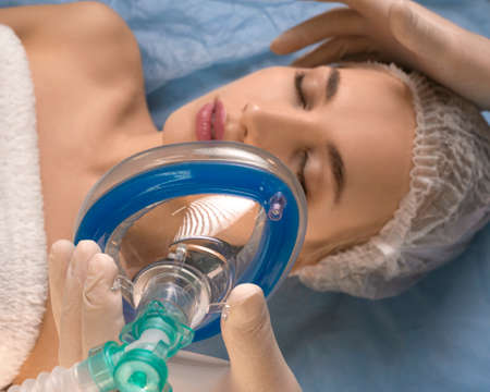 Close-up - the doctor gives anesthesia to the patient before surgery or beauty procedure. Focus on the mask. Stock fotó