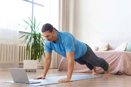 Middle-aged man doing push-ups in front of laptop. He uses an online tutorial from the internet to monitor the workout.