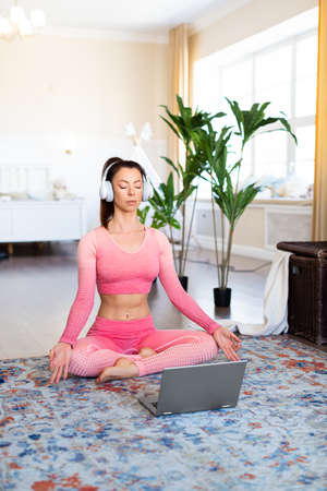 Vertical photo of a woman meditates at home in front of a laptop monitor. Online yoga lesson during quarantine.