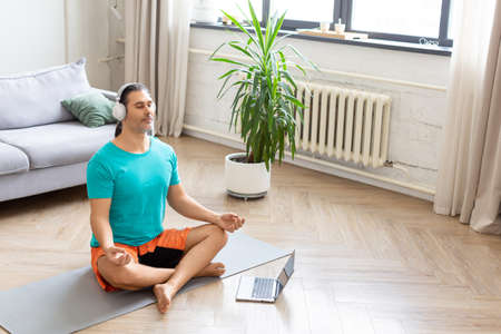 Home workout and healthy lifestyle concept - man meditates at home - using from the internet to monitor the workout. He listens to relaxing meditation music through headphones.