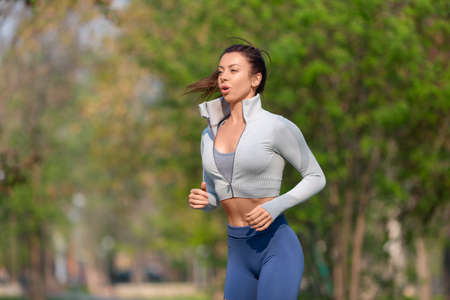 Young woman running in the city park in early morning. Attractive looking woman keeping fit and healthy.