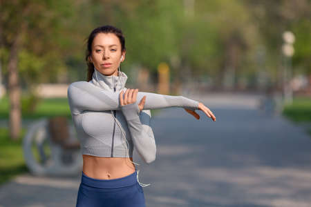 Women stretching shoulders for warming up before running or working out. Young female runner stretching arms before running at morning.