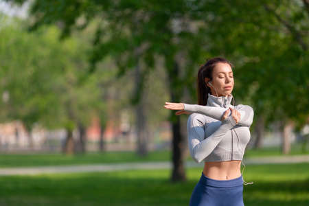 Women stretching shoulders for warming up before running or working out. Healthy lifestyle concept.