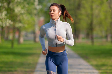 Young woman runs to the music in the city park. Concept of keeping fit and healthy lifestyle.