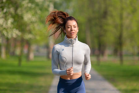 Woman running in park in early morning. Attractive looking woman keeping fit and healthy. Standard-Bild