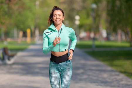 Picture of a woman running in park in early morning. Attractive looking woman keeping fit and healthy.