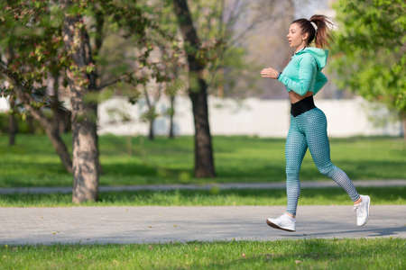 Full length photo of a woman running in park in early morning. Attractive looking woman keeping fit and healthy. Standard-Bild