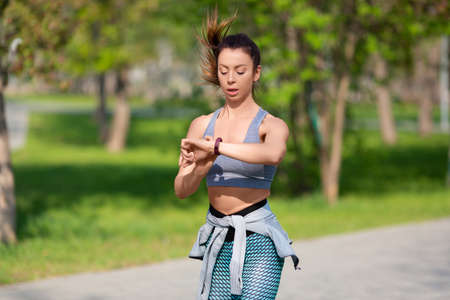 Young woman checks her pulse during the race.