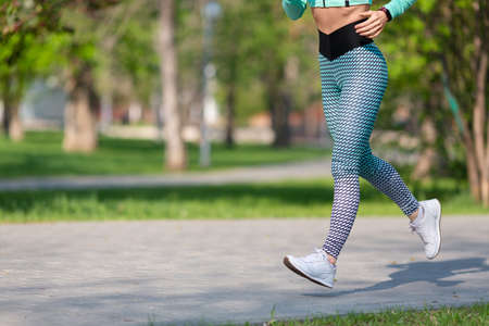 Woman jogging early in the morning in the park. Photo of legs of a running woman close-up. Concept of a healthy lifestyle and keeping the body in shape.