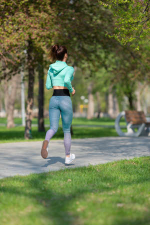 Full length vertical photo of a woman running in park in early morning. Attractive looking woman keeping fit and healthy.